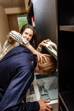 Office revenge. Woman tries to shove the men in the copy machine Stock Photos