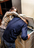 Office revenge. Woman tries to shove the men in the copy machine Royalty Free Stock Photo