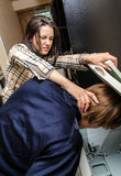 Office revenge. Woman tries to shove the men in the copy machine Royalty Free Stock Images