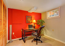 Office room in contrast bright colors. Small office room with contrast red wall, beige carpet floor and small window. Furnished with small desk and whirlpool royalty free stock images