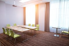 Office room with green chairs,big and small tables and video projector. Side view image of office room with green chairs,big and small tables and video projector stock photos