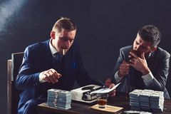 Office routine. Business partners with cash money. Businessmen write financial report while drinking and smoking royalty free stock images