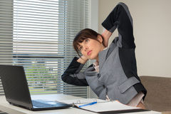 The office routine. The image of business woman doing exercise at the office Royalty Free Stock Photos