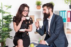 Office rumors. Couple coworkers relax coffee break. Share coffee with with colleague. Flirting colleagues. Bearded man. Office rumors. Couple coworkers relax royalty free stock images