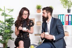 Office rumors. Office coffee. Couple coworkers relax coffee break. Share coffee with with colleague. Flirting colleagues. Bearded men and attractive woman. Man royalty free stock photography