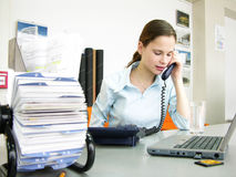 Office scene. A regular office scene. Woman speaking at the phone Royalty Free Stock Images