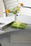 Office scene with flower vase, gift parcel and keyboard on desktop Royalty Free Stock Image