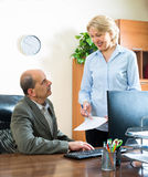 Office scene with two aged co-workers Stock Photos