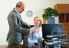 Office scene with two elderly and happy workers. Ordinary office scene with two elderly and happy co-workers stock photo