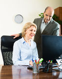 Office scene with two elderly and positive workers Royalty Free Stock Photos