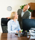 Office scene with two elderly and smiling workers Stock Photography