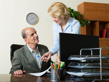 Office scene with two mature   co-workers Royalty Free Stock Photo