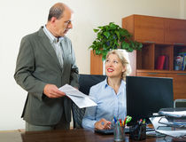 Office scene with two mature and positive workers Royalty Free Stock Photos