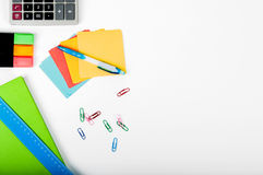 Office, school, business, education and technology concept - clo. Se up of notebook, paper stickers, pencil, clip, calculator, different stuff on white Royalty Free Stock Image