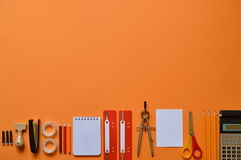 Office or school supplies on orange paperboard. As border with copy space Stock Image