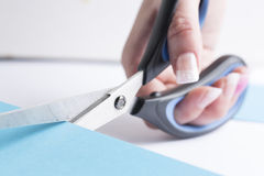 Office scissor cutting a blue cardboard Stock Images