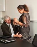 Office sexual harassment. Secretary defending herself with her scissors against intimacy by her boss Stock Photos