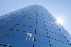 Office skyscraper building. With sun rays on the right, on blue sky background Stock Image