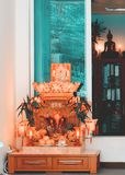 Office with small Buddhist altar in Bangkok. The inside of a building or office with a small Buddhist altar and statues in Bangkok,Thailand Stock Photo