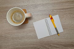 Office space with an empty note book at coffee time looking for inspirational ideas. Desktop from above. Office space with an empty note book at coffee time Stock Photos