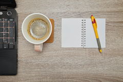 Office space with an empty note book at coffee time looking for inspirational ideas. Desktop from above. Office space with an empty note book at coffee time Stock Images