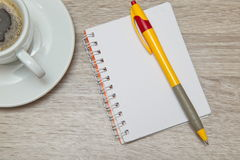 Office space with an empty note book at coffee time looking for inspirational ideas. Desktop from above. Office space with an empty note book at coffee time Royalty Free Stock Photography