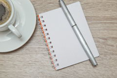 Office space with an empty note book at coffee time looking for inspirational ideas. Desktop from above. Office space with an empty note book at coffee time Royalty Free Stock Images