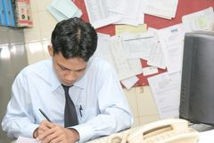 Office staff. Man in messy office working serious stock image