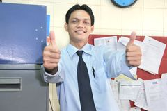 Office staff. Man in office showing thumb up smiling royalty free stock photography