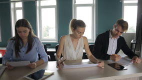 Office staff work in a row at same table, looking at documents, and in tablet screen. Two seated young women, studying graphic documents and texts, sits a man stock footage