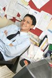 Office staff worker. Man in messy office pose smiling royalty free stock image