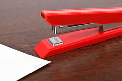 Office stapler. On wooden table Royalty Free Stock Photos