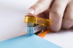 Office stapler ready to staple paper. Orange office stapler ready to staple blue paper Royalty Free Stock Images