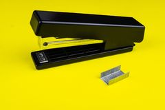 Office stapler and staples. Stationery stapler and staples on yellow background royalty free stock photography