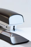 Office stapler stapling white paper. Closeup of a grey office stapler stapling white paper Royalty Free Stock Photography
