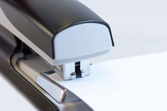 Office stapler stapling white paper. Closeup of a grey office stapler stapling white paper Royalty Free Stock Images