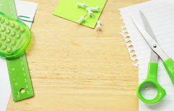 Office Stationary. And equipment;scissors,calculator,ruler,push pins and paper on a wooden desktop background Stock Images