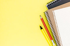 Office stationary with two clean notebooks and sheet of paper on. Yellow, top view Royalty Free Stock Image