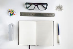 Office stationery and notebook for writing text. Office stationery such us glasses, pen, stapler, paper clip, ruler and notebook for writing text Stock Photo