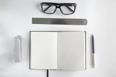 Office stationery and notebook for writing text. Office stationery such us glasses, pen, stapler, ruler and notebook for writing text Stock Images