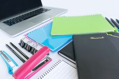 Office and Stationery Supplies and a Laptop. Multiple stationery items for office and school and a laptop from corner perspective Royalty Free Stock Image