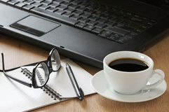 Office still life. Laptop, notepad, pen, glasses and cup of coffee on wooden desk Royalty Free Stock Photo