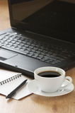 Office still life. Laptop, notepad, pen and cup of coffee on wooden desk Stock Photography