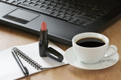 Office still life. Laptop, notepad, pen, lipstick and cup of coffee on wooden desk Stock Photography