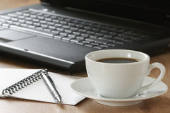 Office still life. Laptop, notepad, pen and cup of coffee on wooden desk Royalty Free Stock Photography