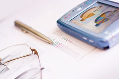 Office still life. Closeup of office objects - glasses, pen, graph, statistics, pda Royalty Free Stock Images