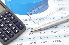 Office still life close-up. Close-up of calculator, pen and rule on paper table with graph Royalty Free Stock Photo