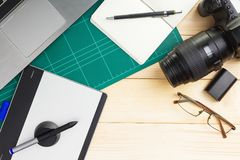 Office stuff and gadgets on wooden desk. Top view of office stuff and gadgets on wooden desk with graphic designer equipment. flat lay style royalty free stock images