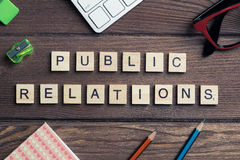 Office stuff and Society public relations idea spelled with bloc. Concept of public relations collected of wooden game elements Royalty Free Stock Image