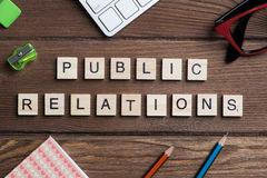 Office stuff and Society public relations idea spelled with blocks. Concept of public relations collected of wooden game elements Royalty Free Stock Photos